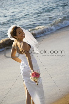 Bride standing on beach.