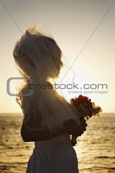 Bride at sunset holding bouquet on beach.