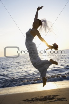 Bride jumping on beach.
