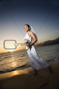 Bride walking holding bouquet on beach.