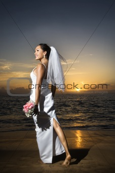 Bride standing holding bouquet on beach.