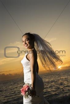 Bride holding bouquet on beach.