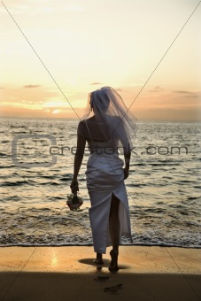 Bride standing on beach at sunset.