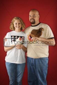 Caucasian male and female holding chickens.