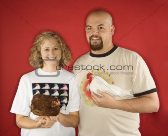 Caucasian man and woman holding chickens.