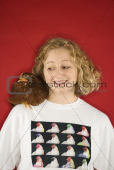 Caucasian woman  looking at chicken on shoulder.