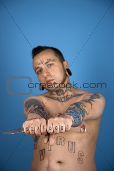 Adult male with tattoos and piercings holding knife.