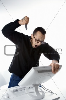 Adult male stabbing computer with knife.
