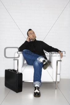 Adult male talking on cell phone with briefcase.