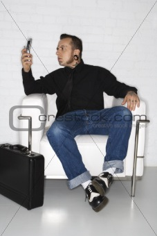 Adult male looking at cell phone with briefcase.