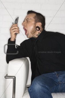 Adult male yelling into cellphone.