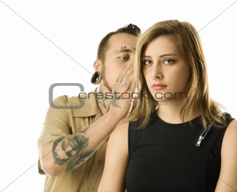 Caucasian male whispering into ear of teen female.