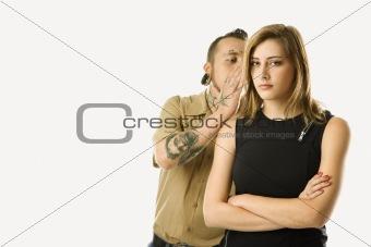 Caucasian male whispering into ear of teen female.