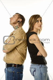 Caucasian male and teen female standing back to back.