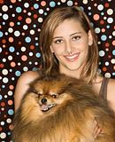 Caucasian teen female holding Pomeranian dog.