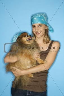 Caucasian teen female holding Pomeranian dog.