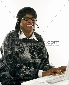 Adult female wearing headset typing on computer.