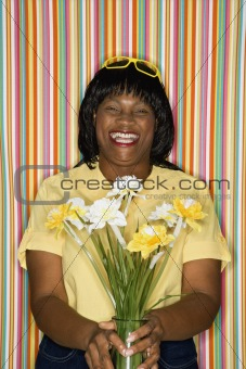 Adult female laughing holding flowers.