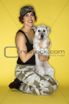 Adult female kneeling holding small white dog.