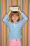 Girl balancing books on head.