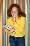Girl holding books and holding finger to lips.