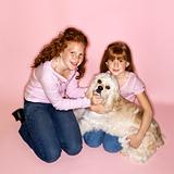 Girls holding Cocker Spaniel dog.