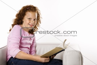 Girls sitting reading book.