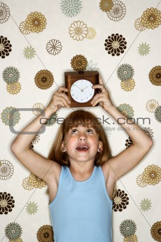 Girl holding clock over head.