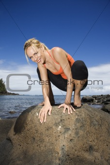 Woman squatting on large rock.