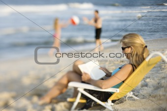 Mom reading in lounge chair on beach.
