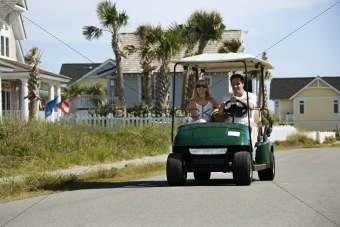 Dad driving golf cart with mom beside him.