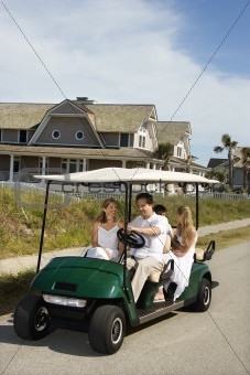 Family riding in golf cart.
