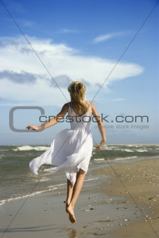 Pre-teenage girl running down the beach.