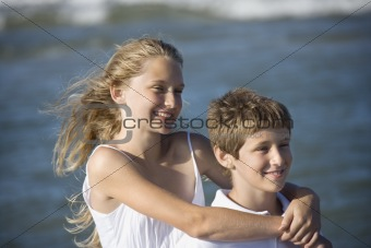 Sister hugging her brother with ocean in background.