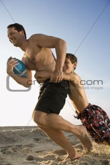 Boy tackling his dad playing football.
