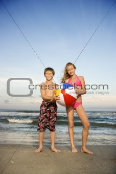 Boy and girl holding beachball on beach.