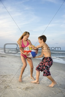 Boy and girl pulling on beachball.
