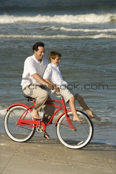 Dad riding bike with son on handlebars.