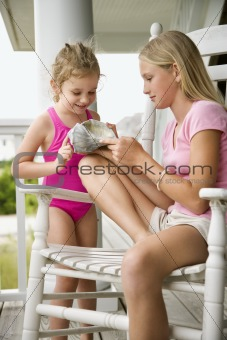 Image 269677: Older girl showing conch shell to younger girl.