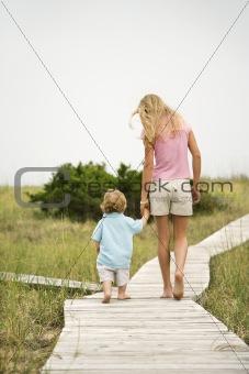 Girl walking on beach walkway with little boy.