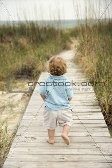 Little boy walking down beach walkway.