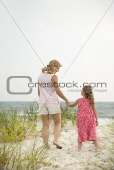 Mom and daughter walking on beach.