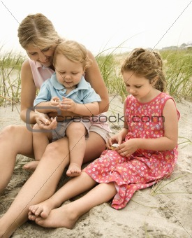 Mom, daughter and son looking at shells.