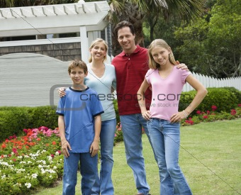 Portrait of family outside in yard.