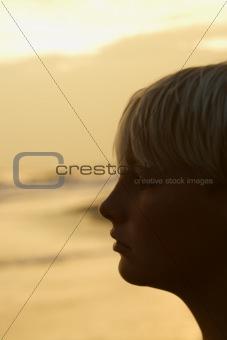 Boy on beach at sunset