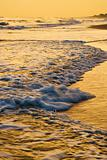 Waves lapping on beach at sunset.