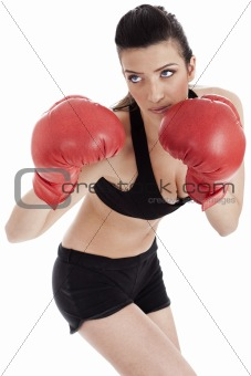 Sporty girl in boxing gloves punching