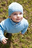 Portrait of a kid in blue walking in the spring meadow