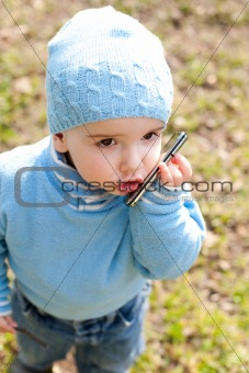 Toddler in blue speaking over the phone
