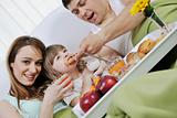 happy young family eat breakfast in bed